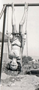 Joan, as a child, hanging on a swingset
