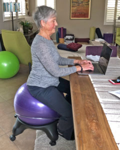 Joyce sitting with pelvis in neutral on ball chair while working on computer