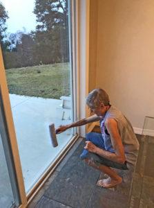 Joan washing patio window in a squat
