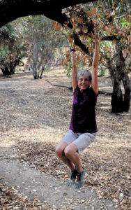 Joan hanging from a tree branch